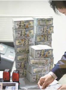 3 황금의 삼각주은행의 창구 내부. 지폐를 세고 있는 직원 옆에 쌓여 있는 100달러 지폐 다발이 눈길을 끈다.[사진 DPRK360]